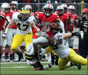 Ohio State wide receiver Corey Brown, center, attempts to elude Michigan linebackers Kenny Demmens, right, and Jake Ryan on Saturday in Columbus. Ohio State won 26-21.