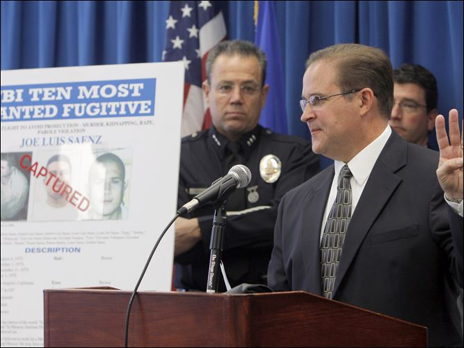 FBI Most Wanted-Arrest Bill Lewis, the FBI Los Angeles Assistant Director in Charge, right, and Los Angeles Police Assistant Chief Michael Moore, left, today announces the arrest of suspect Joe Luis Saenz, one of the FBI Ten Most Wanted fugitives, Thursday.