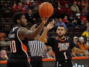 BGSU's Jehvon Clarke, left, gives the ball to the ref as Jordon Crawford high-fives him at end of the game against Detroit.
