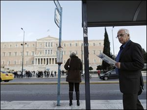 A man reads a newspaper as he walks past a bus stop opposite the Parliament in central Athens today.