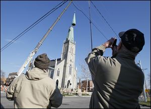 Workers from the Speiker Company install a new steeple on St. Rose Church.