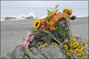 Flowers are rest on a large drift log yards from the breaking surf of the Big Lagoon beach near Trinidad, Calif., Monday.