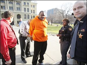 An unidentified man is one of a handful of people taken into custody by Lucas County Deputies after a disturbance in the on in front of the Lucas County Courthouse.