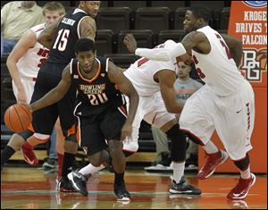 The Falcons' Jehvon Clarke dribbles the ball past Doug Anderson, right, after pulling down a rebound.
