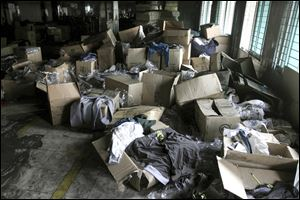 Boxes of garments are piled near equipment charred in the fire that killed 112 workers Saturday at the Tazreen Fashions Ltd. factory, on the outskirts of Dhaha, Bangladesh. Some of the major retailers said the merchandise was being produced without their approval.