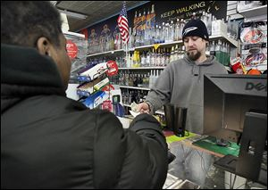 SLUG: CTY lottery                               Date: 11/28//2012 Toledo Blade/ Amy E. Voigt             Toledo, Ohio  CAPTION: Matt Opperman, right, Manager of  Ray's Party Store  on Main St., sells a Powerball tickets to Felicia Neal, left, from Toledo, on November 28, 2012. The size of tonight's jackpot has risen to about  $550 million by the afternoon.