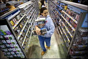 A shopper loaded down with purchases makes her way through the aisles at Best Buy in Bowling Green, Ky., at the start of the Thanksgiving shopping weekend. U.S. consumer confidence rose this month to its highest level in almost five years, the Commerce Department reported Tuesday.
