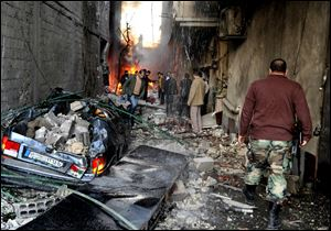 A Syrian soldier, right, and citizens gather at an alley that was destroyed by two cars bombs, at Jaramana neighborhood, in the suburb of Damascus, Syria.