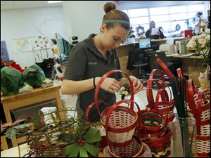 Tori Yeager, 18, of Swanton, works on crafting a custom holiday corsage for a client.