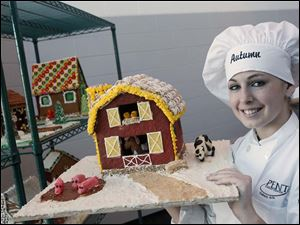 Autumn Nagy, 17, of Elmwood High School, holds her gingerbread barn. The students' gingerbread houses will be displayed at both the Imagination Station and the Toledo Zoo.