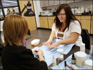 Kristi Sager, of Rossford, right, takes a look at her finished nails after receiving a manicure from Penta student Jamie Marsh, 18, of Eastwood High School, left.