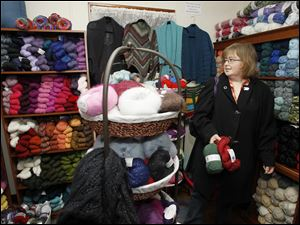 Kris Pettee of Toledo, shops for green and red yarn during an open house at Yarn Cravin' in Perrysburg.