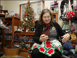 Sandy Scharlow of Toledo, works on a Christmas tree skirt for a gift.