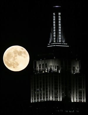 A full moon rises near the Empire State Building, as seen from Hoboken, N.J. on Wednesday.