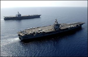 U.S. Navy aircraft carrier USS Enterprise, foreground, steams through the Red Sea with the USS Dwight D. Eisenhower in 2006.