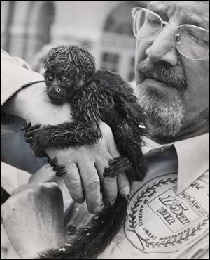 Mr. Klewer, a former zoo director, shows off a monkey after safari members returned to the Toledo Zoo.