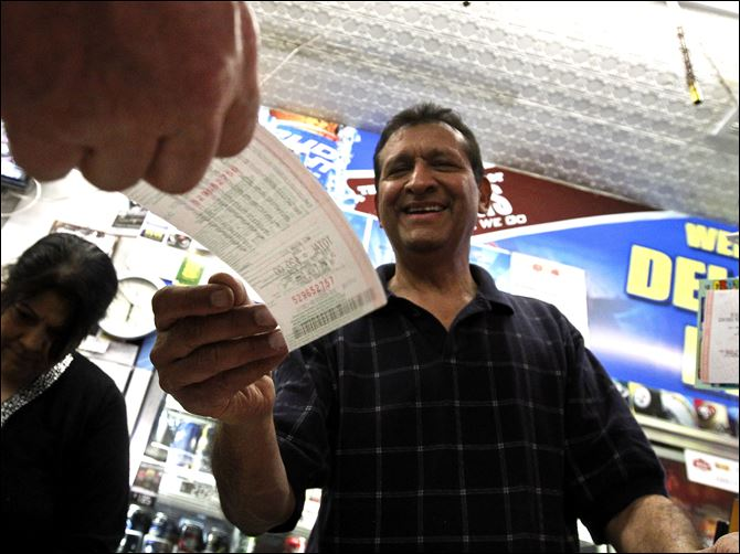 As he hands over a customer's lottery ticket As he hands over a customer's lottery ticket, Keith Ganatra, right, and his wife Anita Ganatra, left, owners of the Del Monte Market, help the long line of customers inside their store waiting to buy Powerball lottery tickets Wednesday, in Phoenix.