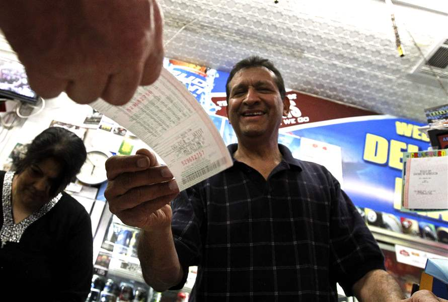 As-he-hands-over-a-customer-s-lottery-ticket