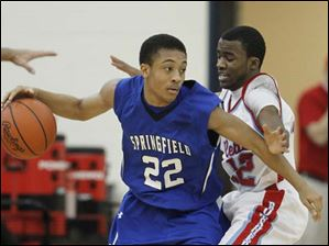 Springfield High School player Markese Hicks, 22, is defended by Bowsher High School player Scotshaun Shores, 12.