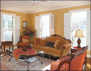 Classic white plantation shutters allow abundant sunlight into the formal parlor.