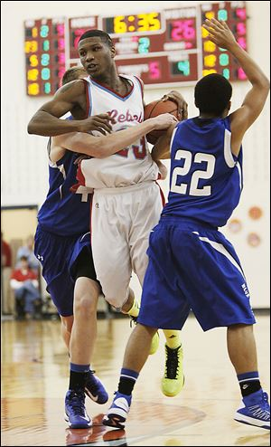 Bowsher's Nate Allen, who led all scorers with 21 points, runs into Springfield's Chad Roy, left, and Markese Hicks.