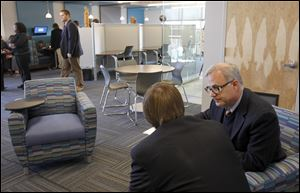 Theology teacher Mike Wielgopolski helps senior Alex Lincoln prepare for an exam at the new Student Achievement Center at St. Francis de Sales High School. The 6,000-square-foot center, dedicated on Thursday, has SMART boards, computers, flatscreen TVs, and few physical books.