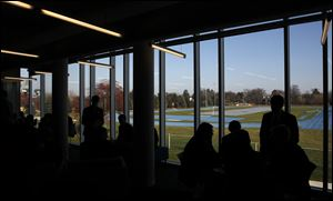 Students mingle near the large glass windows in the Student Achievement Center that overlook the track. The center was created by combining two classrooms and the library. It was built as an addition to the main building.