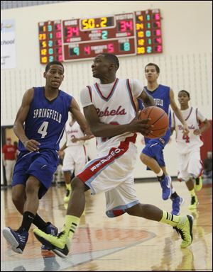 Bowsher High School player Dajuan King, 13, drives against Springfield High School player Marquan Hodges, 4, during the second quarter at Bowsher High School.