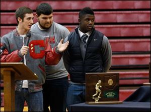 Central Catholic captains from left Ian Butler, Mitch Cochell, Jeff Dew, and Amir Edwards present the state championship trophy, the regional championship trophy, and the Irish Knight to the school.