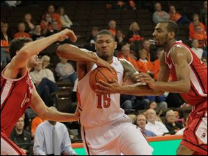 BGSU's A'uston Calhoun drives to the basket between YSU defenders Josh Chojnacki, left, and Damian Eargle.