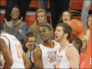 BGSU teammates Craig Sealey, center, and James Erger, right, and the fans react after Richaun Holmes, left, scores two and gets the foul.