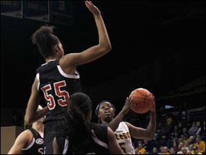 SIU's Raven Warford, #55, and Tierny Austin guards UT's Janelle Reed-Lewis as she drives to the basket.