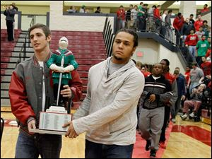 Central Catholic captains Mitch Cochell, left, and Ian Butler carry the Irish Knight into the gym.