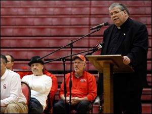 Father Dennis Hartigan speaks during a rally for the Central Catholic High School football team.
