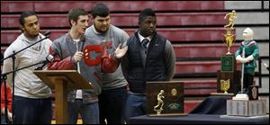 Central Catholic High School football team captains from left to right Ian Butler, Mitch Cochell, Jeff Dew, and Amir Edwards present the team's trophies to the school.