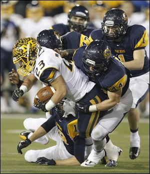 Cincinnati Moeller'S Joe Eramo, 23, is tackled by Whitmer'S Jack Linch, 44, Al Bryant, IV and Devin Thomas, 1, during the second quarter Saturday.