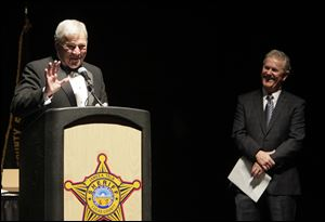 Lucas County Sheriff James Telb, at podium, with Sheriff-elect John Tharp, right, during a retirement party at the SeaGate Convention Centre in honor of Sheriff Telb, who is about to retire.