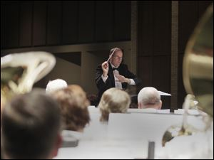 Kevin Heidbreder, director of the Maumee Community Band conducts during