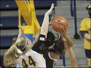 UT's Kyle Baumgartner, left, and Inma Zanoguera, right, attempt to block Hannah Little's shot.