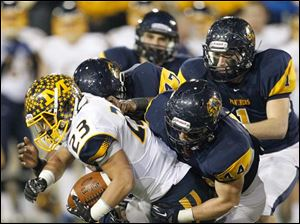 Cincinnati Moeller High School player Joe Eramo, 23, is tackled by Whitmer High School player Jack Linch, 44, Al Bryant, IV and Devin Thomas, 1.