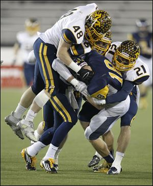 Whitmer's Nate Holley is tackled by Cincinnati Moeller's Paul Barron, left, Sam Hubbard, and Chris Kessling in  the second quarter of the Division I state championship game in Canton.