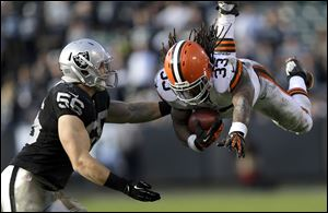 Cleveland Browns running back Trent Richardson, right, leaps in front of Oakland Raiders linebacker Miles Burris during the third quarter Sunday in Oakland, Calif. The Browns won 20-17, snapping a 12-game road losing streak.
