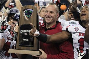 Northern Illinois coach Dave Doeren holds the Mid-American Conference championship trophy after his team defeated Kent State 44-37 in double overtime Friday in Detroit. Doeren has since left to accept the job at North Carolina State, but he did lead the Huskies to a BCS berth this season.
