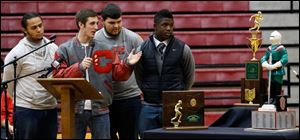 Team captains, from left, Ian Butler, Mitch Cochell, Jeff Dew, and Amir Edwards present trophies to the school. The awards are the regional and state championships and the Irish knight.