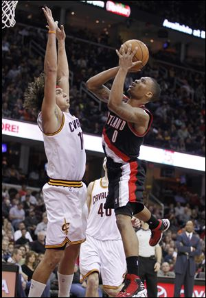 Portland Trail Blazers' Damian Lillard (0) shoots over Cleveland Cavaliers' Anderson Varejao (17), from Brazil, in the third quarter Saturday. Lillard scored a team-high 24 points in the Trail Blazers' 118-117 win.