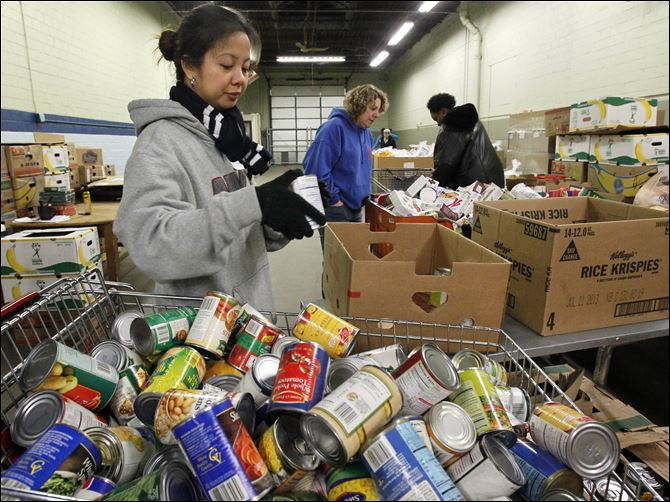 MAG FoodMag mylene mendoza Volunteer Mylene Mendoza checks expiration dates on canned goods for clients at the Toledo Seagate Food Bank.