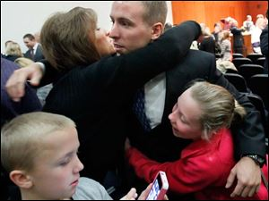 CTY swearingin04p  Ryan Parquette gets a hug from his mother, JoAnn Grindle, and his sister, Rylee Gridle, 12, after being sworn in as a member of the Toledo Fire and Rescue Department, during a ceremony at One Government Center, Monday, December 3, 2012.  Jarrett Grindle, 10, his brother, is in foreground.  THE BLADE/DAVE ZAPOTOSKY