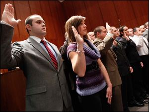Recruits including Jake Hoffman, left, and Tanya Jarzynski, are sworn in as members of the Toledo Fire and Rescue Department.