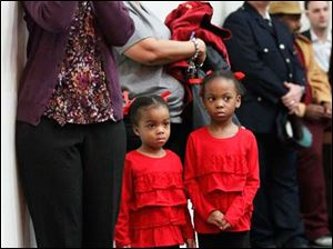Raiyn Roberts, 3, left, and her sister, Riayn Roberts, 4, watch as their father, Ronald Roberts, Jr., is sworn in. The girls' grandmother, Janet Roberts, is behind them.