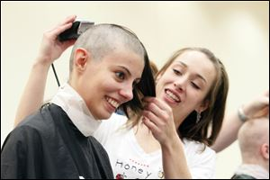 Briana D'Entremont, 19, has her head shaved by Haylee Keel of Honeycomb Salon and Spa during a fund-raiser for St. Baldrick's Foundation, which funds childhood cancer research grants, at BGSU.